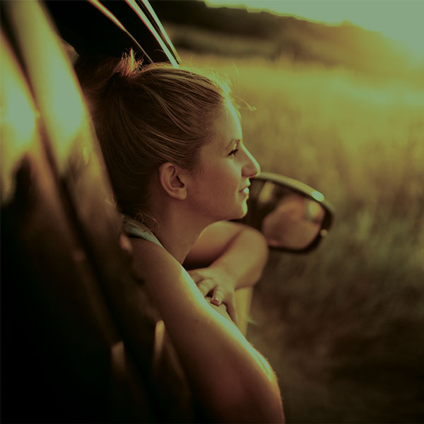 Woman looking out window of car door